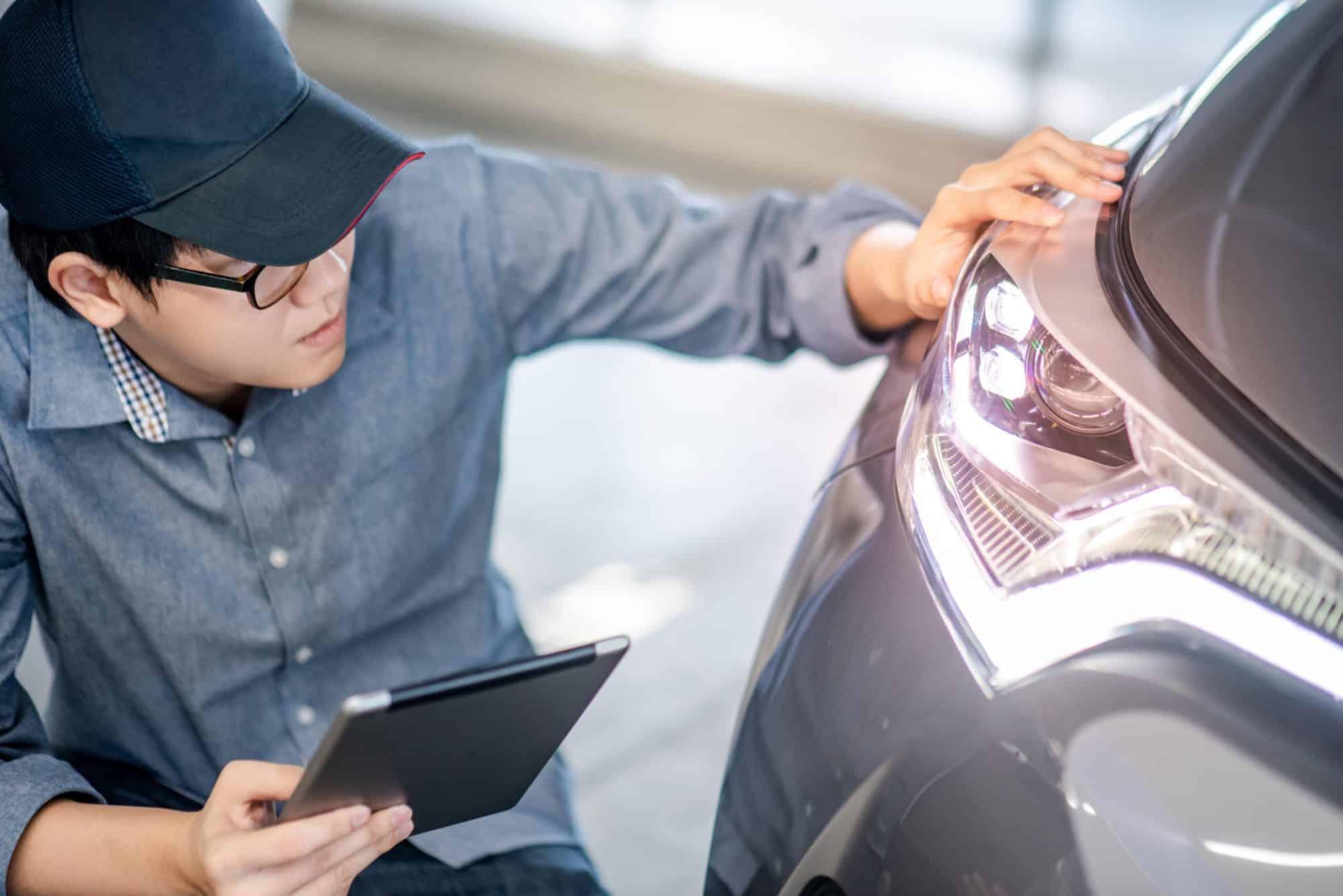 young-man-checking-car-headlights