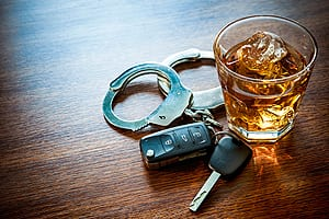 Car Keys & Handcuffs Laying Next To A Glass Of Alcohol