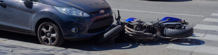 Motorcycle Accident With Navy Blue Vehicle Stock Photo