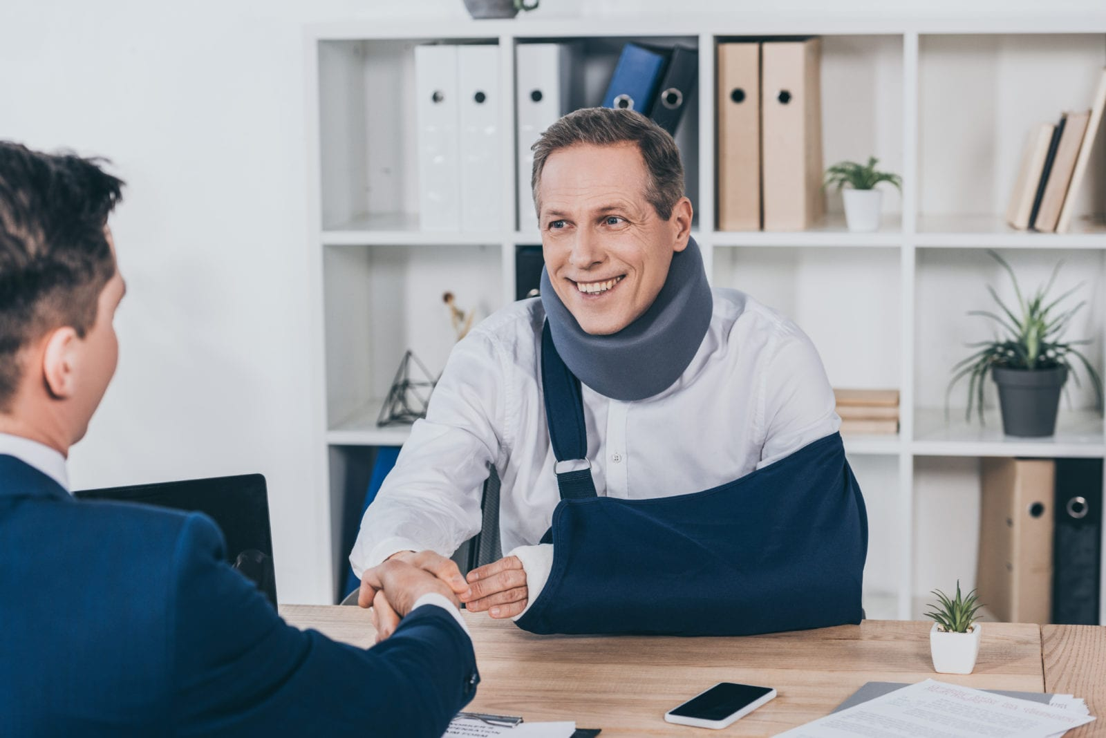 worker in neck brace with brokenarm and businessman in blue jacket shaking hands over table in office, compensation concept