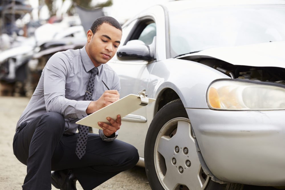insurance adjuster inspecting damage after a car accident
