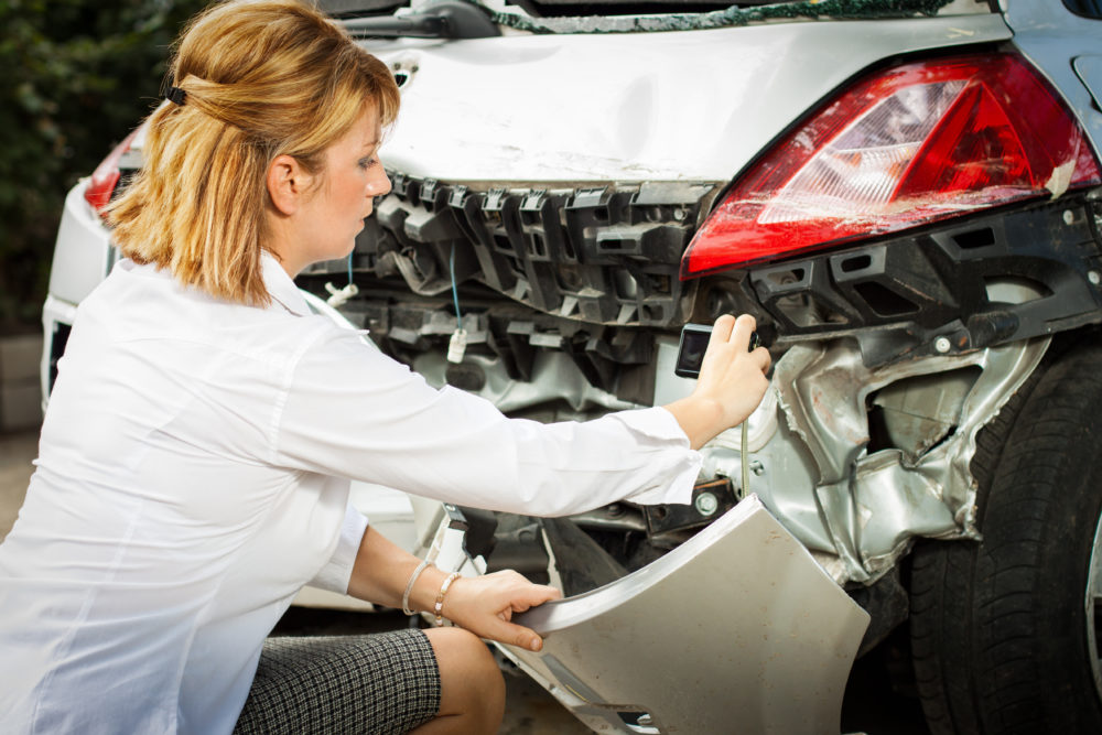 an insurance adjuster inspecting the damage to a car after an accident