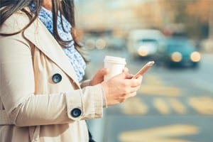 Woman Using Mobile Device While Walking Across The Street