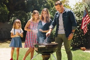 Family Hosting A Cookout Outdoors Stock Photo