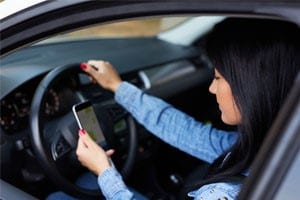 woman looking at phone GPS while driving
